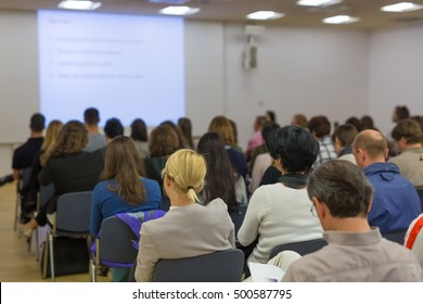 Speaker Giving a Talk at Business Meeting. Audience in the conference hall. Business and Entrepreneurship. Focus on unrecognizable people from rear.