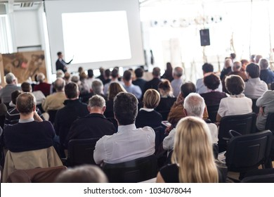 Speaker giving a talk in conference hall at business event. Audience at the conference hall. Business and Entrepreneurship concept. Focus on unrecognizable man in the audience.