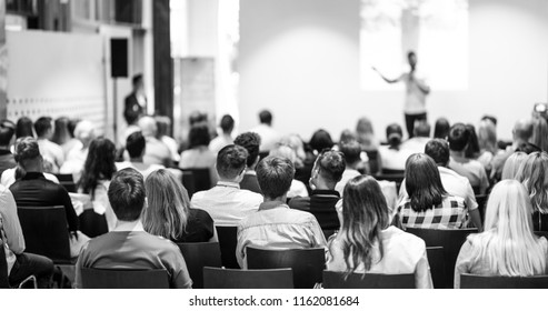 Speaker giving a talk in conference hall at business event. Focus on unrecognizable people in audience. Business and Entrepreneurship concept. Black and white image.