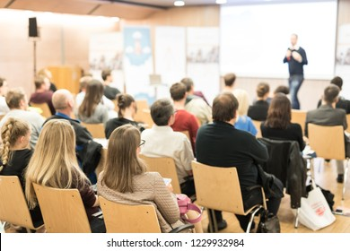 Speaker giving a talk in conference hall at business event. Audience at the conference hall. Business and Entrepreneurship concept. Focus on unrecognizable people in audience.