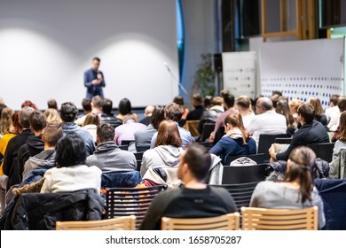 Speaker giving a talk in conference hall at business event. Rear view of unrecognizable people in audience at the conference hall. Business and entrepreneurship concept.