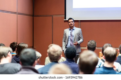 Speaker giving a talk in conference hall at business meeting event. Rear view of unrecognizable people in audience at the conference hall. Business and entrepreneurship concept.