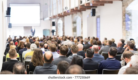 Speaker giving a talk in conference hall at business event. Audience at the conference hall. Business and Entrepreneurship concept. Focus on unrecognizable businessman in the audience.