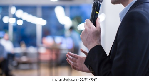 """""""Speaker giving a talk at a corporate business conference. Audience in hall with presenter in front of presentation screen. Corporate executive giving speech during business and entrepreneur seminar."""