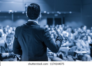 Speaker giving a talk on corporate business conference. Unrecognizable people in audience at conference hall. Business and Entrepreneurship event. Blue toned grayscale image.