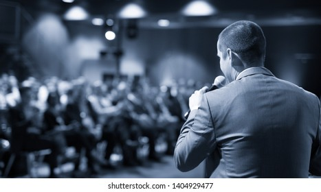 Speaker giving a talk on corporate business conference. Unrecognizable people in audience at conference hall. Business and Entrepreneurship event.
