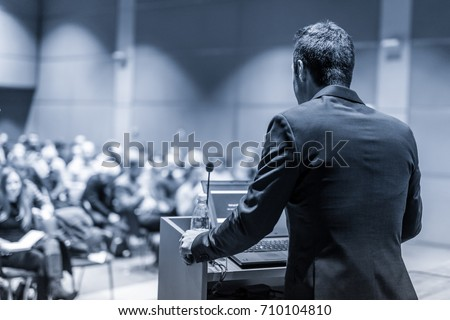 Speaker giving a talk on corporate Business Conference. Audience at the conference hall. Business and Entrepreneurship event. Black and white blue toned image.