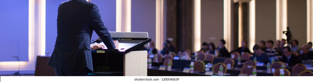 Speaker with Hands and Arms on Podium at Corporate Conference. Expert Lecture by Business Management at Hall. Leadership Symposium Event for Future Leaders.