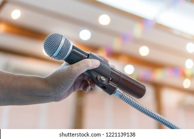 Speaker holding microphone for speak, presentation on stage in public conference seminar room. Business meeting and education in teaching classroom concept. Event light convention hall Background