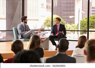 Speaker and interviewer talk in front of audience at seminar
