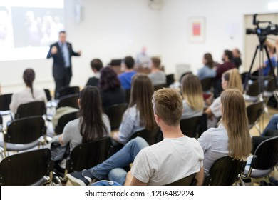 Speaker lecturing in lecture hall at university. Students listening to lecture and making notes.
