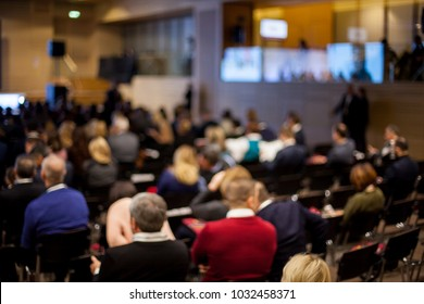 Speaker on the podium. People at conference hall, rear view. Speaker at Business Conference and Presentation. Audience at the conference hall. Abstract blurred photo of conference hall.