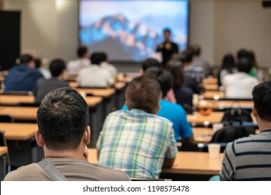 Speaker on the stage in front of the room with Rear view of Audience in put hand up acton for answer the question in the meeting or seminar meeting, business and education concept