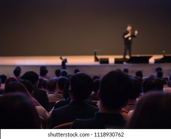 Speaker on Stage Presenting at Event. Audience at Conference Hall Lecture Series. Corporate Technology Investors. Tech Managers Pitch. Blurred De-focused.