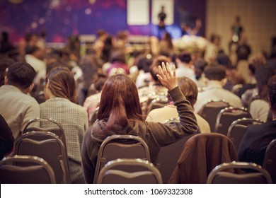 Speaker on the stage with Rear view of Audience in put hand up acton for question in the meeting or seminar meeting, business and education concept
