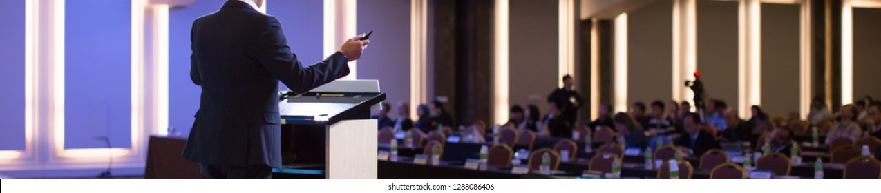 Speaker at Talk in Business Conference. Corporate Speaker on Stage at Seminar. Presenter Giving Business Presentation at Meeting. Corporate Exhibition for Investors Event.