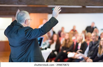 Speaker talking at Business Conference. Audience at the conference hall blured in background. Rear view. Horisontal composition.