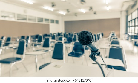 Speaker's microphone in educational event, conference lecture hall or seminar meeting room with audience or school student