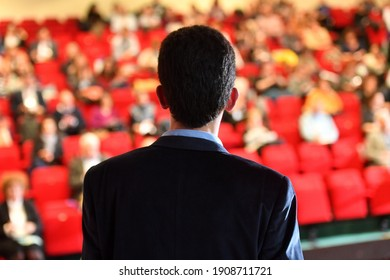 Speakers. The person speaking in front of a room, presentation.