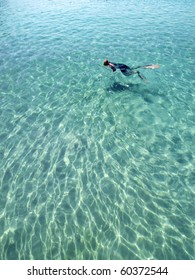 Spear fisherman hunting in shallow tropical lagoon