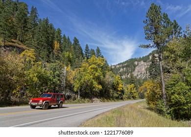 SPEARFISH, SOUTH DAKOTA, September 26, 2018 : A red car drives in a fall landscape of Spearfish Canyon.