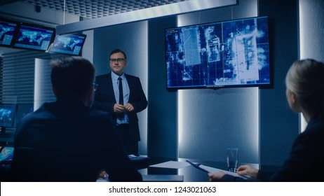 Special Agent in Charge Shows Satellite Surveillance Footage of the Car Getaway to a Team of Government Agents. GPS Tracking Fugitive in the Big Monitoring Room Full of Computers with Animated Screens