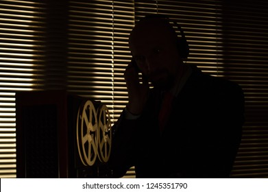 Special agent intelligence officer listens to conversations and records on a reel to reel tape recorder 4