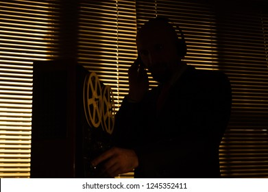 Special agent intelligence officer listens to conversations and records on a reel to reel tape recorder 5
