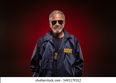 Special agent, wearing his windbreaker and badge, smirking with confidence.