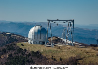 A special astrophysical observatory and a crane against the background of the blue sky and Caucasian mountains.