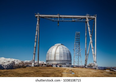 A special astrophysical observatory and a crane against the background of the blue sky and snowy peaks of the Caucasian mountains.