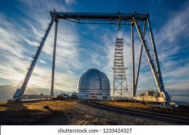 A special astrophysical observatory and a crane against the background of the sunset sky and snowy peaks of the Caucasian mountains.