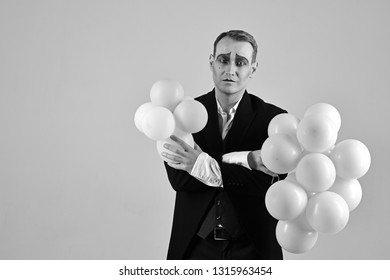 Special day to celebrate. Mime man with party balloons. Balloon artist. Man with mime makeup on birthday party. Happy birthday or anniversary celebration. Holding festive celebration, copy space.