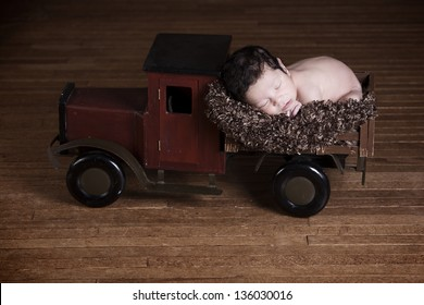 Special Delivery.  Adorable biracial newborn fast asleep in the back of a wooden toy truck.