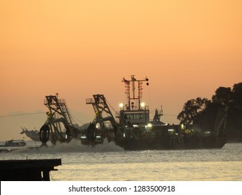 Special dredge ship works at evening for reclamation project to create new land at Losari beach, Makassar, South Sulawesi, Indonesia.