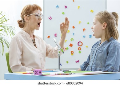 Special education teacher working with little girl during speech therapy