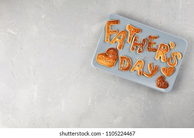 Special Father's Day breakfast. Alphabet Pancakes with sprinkles on blue rectangular plate. Top view, copy space on a gray concrete background