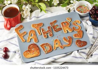 Special Father's Day breakfast. Alphabet Pancakes with sprinkles, cherries and cup of tea on a gray concrete background with apple blossom branch. Closeup view, selective focus