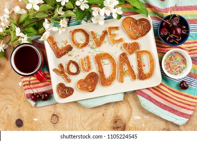 Special Father's Day breakfast. Alphabet Pancakes with sprinkles, cherries and cup of tea on wooden background with apple blossom branch. Closeup view