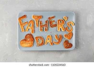 Special Father's Day breakfast. Alphabet Pancakes with sprinkles on blue rectangular plate. Top view, close up on a gray concrete background