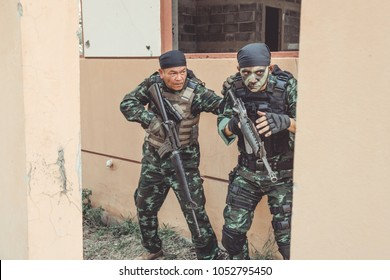 Special force soldiers in urban combat training.  Breach and entry building. Chinese soldiers in full combat gear, green digital cammo.