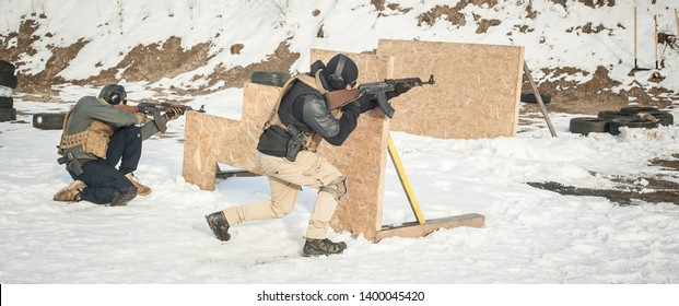 Special forces action shooting and moving defensive rifle firearm use training on outdoor shooting range. Winter and snow cold season