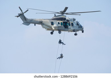 Special forces show with soldier or pilot jump from helicopter with blue sky on background.