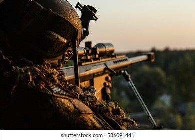 Special forces sniper with large-caliber rifle seeking and killing enemy. Back view sunset sky background