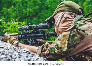 special forces soldier .assault rifle with silencer and optical sight.  behind cover waiting in ambush.