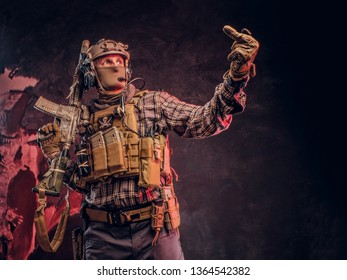 Special forces soldier in camouflage uniform posing with assault rifle, looks sideways and shows the middle finger. Studio photo against a dark textured wall