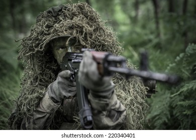 Special forces soldier in heavy camouflage hidden in forest, aiming with assault rifle - focus on eyes
