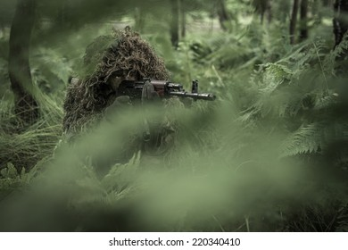 Special forces soldier in heavy camouflage hidden in forest, aiming with assault rifle. Hidden behind trees.