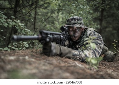 Special forces soldier lying on the ground, preparing to shoot.