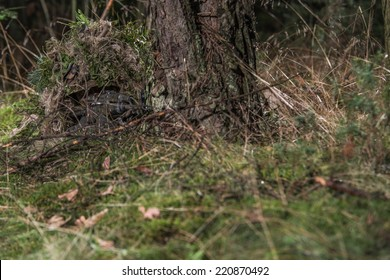 special forces soldier, lying on the ground, covered by ghillie suit, almost invisible in his camouflage, aiming with assault rifle